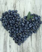 Heart of blueberries on wooden background