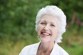 picture of vivacious  - Vivacious laughing grey haired senior woman outdoors in a lush green park close up portrait - JPG