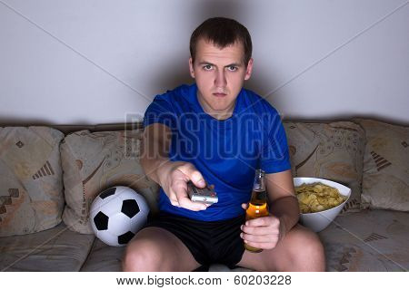 Supporter In Uniform Sitting On The Sofa And Changing Channels With Remote Control