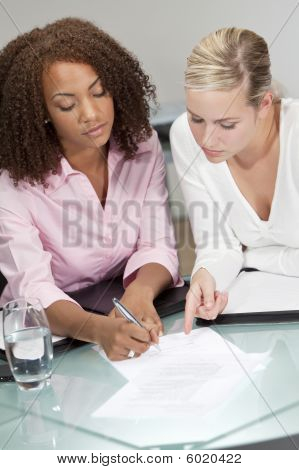 Mixed Race Young Businesswomen Or Lawyers Signing A Contract