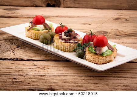 Crostini Vith Mozzarella Cheese Anchowy And Tomato