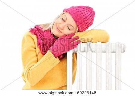 Young female in winter clothes resting on a radiator isolated on white background