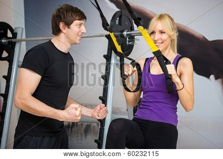 Personal trainer assist woman exercising on at gym