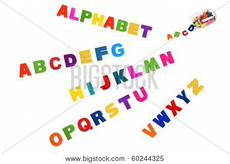 Alphabet Written In Multicolored Plastic Kids Letters And Colorful Symbols Of Alphabet In Glass Can