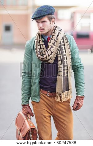 elegant young fashion casual man walking and looking away from the camera