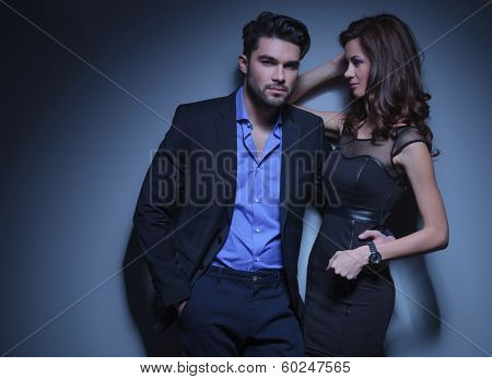 portrait of a young fashion man holding a woman while looking into the camera with his hand in his pocket and while she looks at him. on a dark blue background