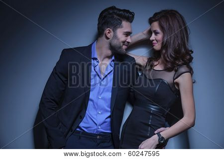 portrait of a young fashion couple laughing while looking into each other's eyes. on a dark blue background