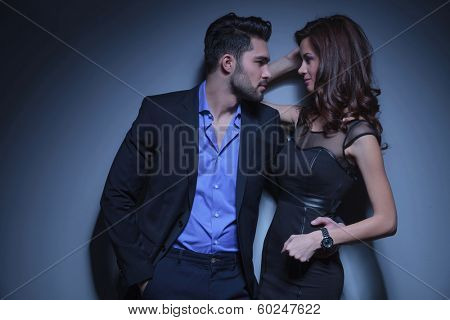 portrait of a young fashion couple looking at each other while the man holds a hand in his pocket and the other on the woman's back. on a dark blue background