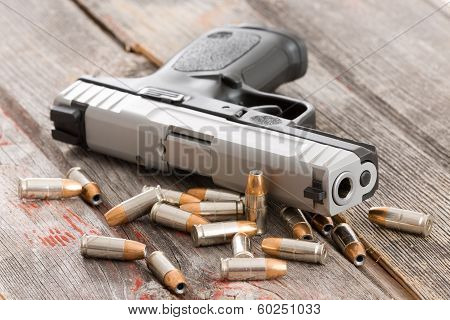 Handgun With Scattered Bullets And