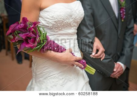 Detail of hands of wedding couple with wedding bouquet