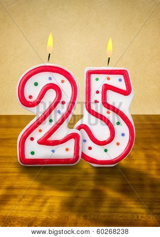 Burning birthday candles number 25 on a wooden background