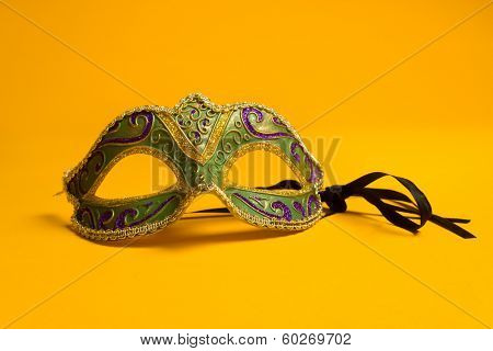 Green, gold, purple mardi gras mask on a bright yellow background