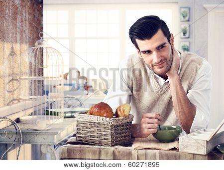 Handsome man having breakfast in trendy cottage style interior, drinking tea, reading newspaper, smiling.