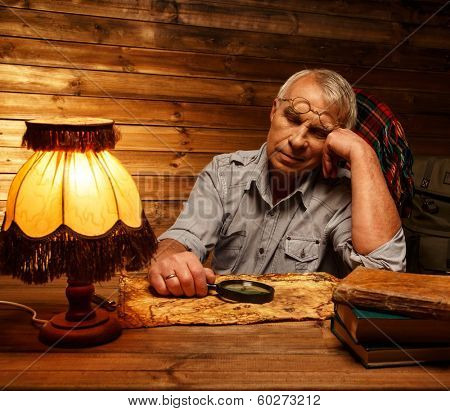 Senior man with magnifier fell asleep in homely wooden interior