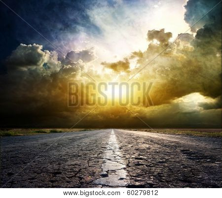 Old asphalt road on the background of Dramatic sunset