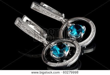 White gold earrings with topazes, isolated on black background