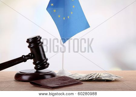 Gavel, money, passport and flag of Europe, on wooden table, on light background