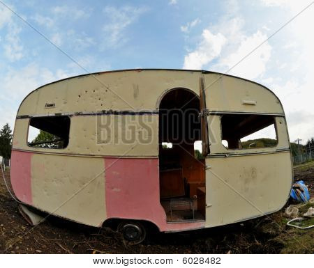 trashed,old caravan/small trailer parked in a dirty backyard