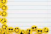 picture of smiley face  - Lots of yellow smiley faces on a lined paper background happy days - JPG