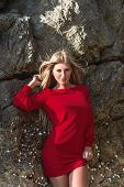 foto of mini dress  - Young fashion blonde woman posing in red mini dress in front of stone background - JPG