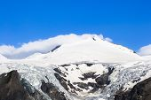 Snowy And Cloudy Mountain Peak With Bright Blue Sky Above