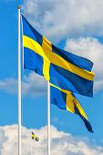 pic of sweden flag  - Three Swedish flags with the flag in front in focus on a typical summer sky in Sweden - JPG