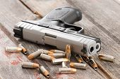 stock photo of handgun  - Close up view of the barrel of a handgun with scattered bullets and cartridges lying on old rustic wooden boards depicting violence crime and robbery with copyspace - JPG