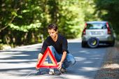 Handsome young man with his car broken down by the roadside, setting the safety triangle