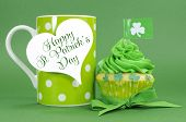 stock photo of irish flag  - Happy St Patricks Day green cupcakes with shamrock flags and green polka dot coffee cup with heart shaped gift tag - JPG