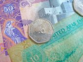 picture of dirhams  - Close-up of a United Arab Emirates shiny coin on top of 10 and 50 dirham banknotes.