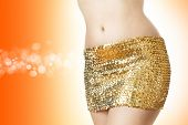 stock photo of mini-skirt  - Disco woman in a golden skirt on orange background - JPG