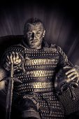 foto of sword  - Portrait of a courageous ancient warrior in armor with sword and shield - JPG