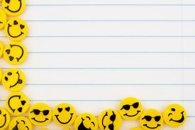 stock photo of smiley face  - Lots of yellow smiley faces on a lined paper background happy days - JPG