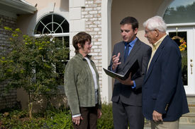 foto of real-estate agent  - real estate agent discussing the options of a new home with potential buyers - JPG