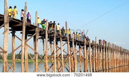 MANDALAY, MYANMAR - JAN 19, 2014: Unidentified group of tourists visiting U Bein bridge. U-Bein bridge is very famous Burmese landmark