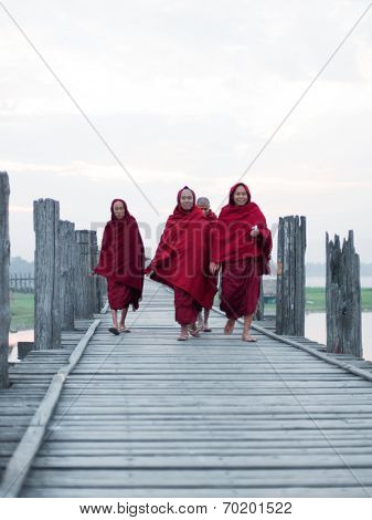 MANDALAY, MYANMAR - JAN 19, 2014: Unidentified monks from local Buddhist temple in Amarapura crossing U Bein bridge at early morning. The bridge is famous historical and cultural heritage of country