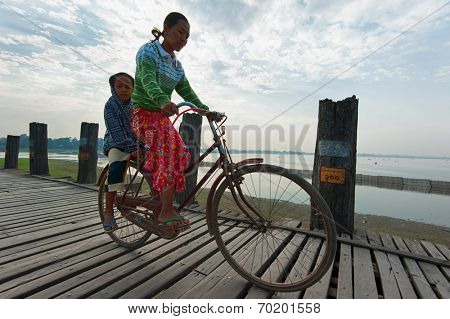 MANDALAY, MYANMAR - JAN 19, 2014: Unidentified Burmese woman and her child crossing U Bein bridge by bicycle at early morning. Thousands of tourists visiting this place annually to meet local people
