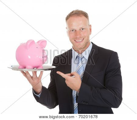 Businessman Showing Piggybank On Tray