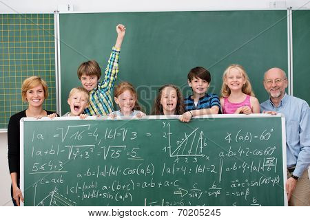 Young Schoolchildren Posing With A Chalkboard