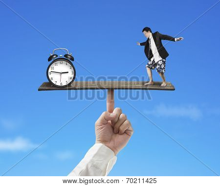 Businessman Standing On Finger Seesaw Vs Clock