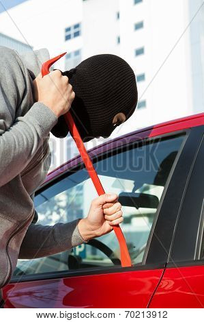 Thief In Hooded Jacket And Balaclava Opening Car's Door