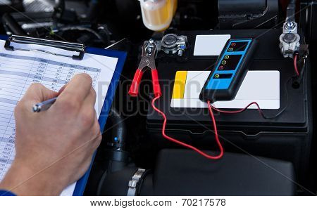 Hand Writing On Clipboard With Pliers Connected To Multimeter