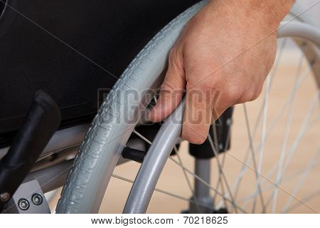 Handicapped Man's Hand Pushing Wheel Of Wheelchair
