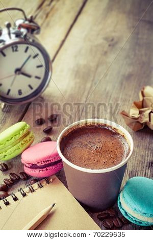 Macaroons, Espresso Coffee Cup, Sketch Book And Alarm Clock On Wooden Rustic Table