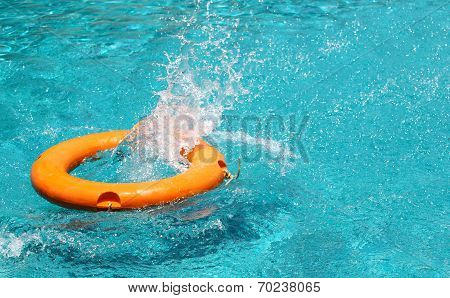 Orange Life Buoy Is Splashing With Clear Blue Water In Swimming Pool