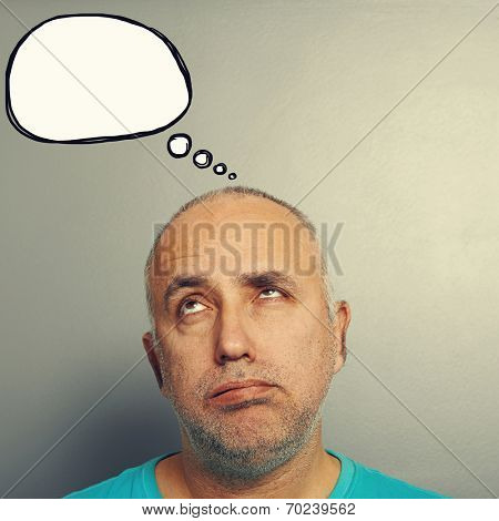 portrait of bored senior man looking up at speech bubble over grey background