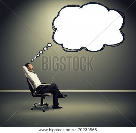 satisfied businessman with laptop resting on the chair and looking at empty speech balloon over grey background