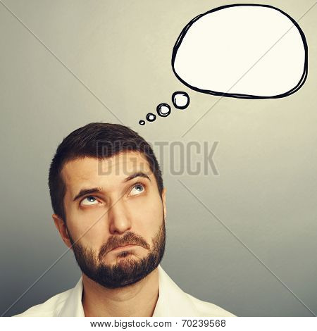 perplexed man looking at empty speech bubble over grey background