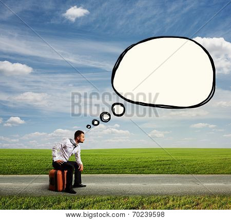 fatigued young man in formal wear sitting on his case and looking forward. photo at outdoor with drawing speech bubble