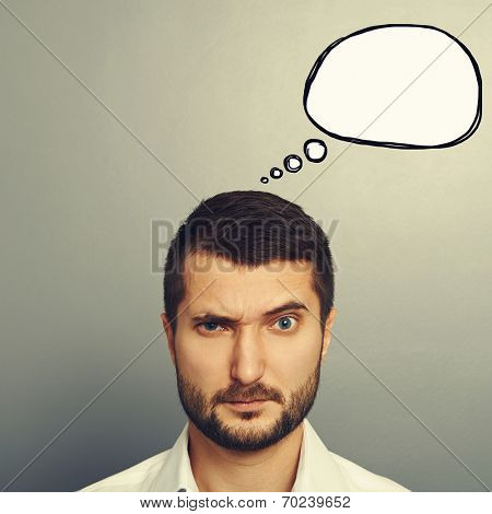pensive man with empty speech bubble looking at camera over grey background